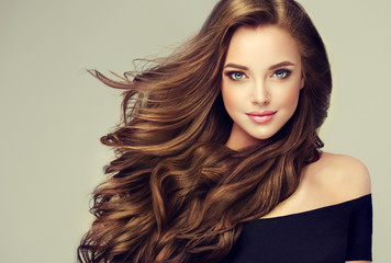 Fotobehang Kapsalon Brunette girl with long and shiny wavy hair . Beautiful model with curly hairstyle .