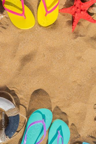 Summer beach scene - frame on sand with sandals\