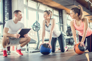 Gym instructor assisting two sporty women with pilates balls in fitness center.