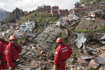 Members of a rescue team look at the destruction after a landslide in the Kupini and Valle de las Flores districts in La Paz