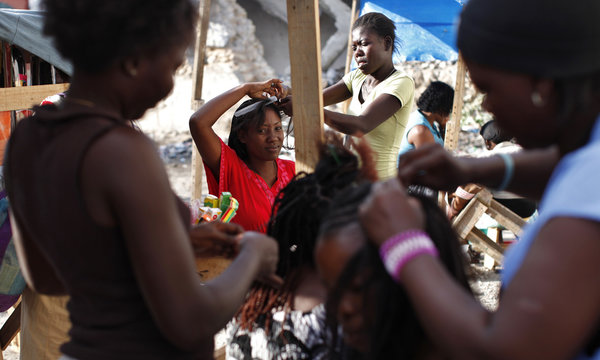 A woman receives hair extensions in downtown Port-au-Prince