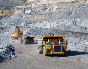 Excavator loading iron ore into heavy dump trucks on the opencast mining site