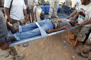Anti-Gaddafi fighters carry a wounded Gaddafi loyalist into an ambulance near Sirte