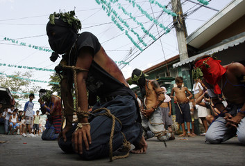 Filipino hooded penitents pray in front of a church during Maundy Thursday Lenten rites in Angeles city