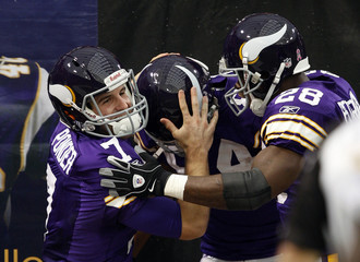 Vikings' Ponder celebrates a long pass reception on the first play of the game with Jenkins and Peterson during their NFL football game against the Packers in Minneapolis