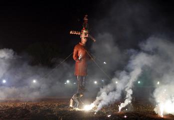 A Hindu man lights firecrackers before an effigy of 10-headed demon king Ravana is burnt during Dussehra festival celebrations in Ahmedabad