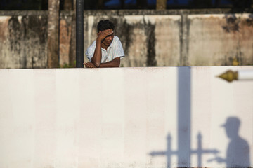 A man looks into the Tsunami Victims Cemetery as a worker painting flag poles casts a shadow outside Ban Nam Khem
