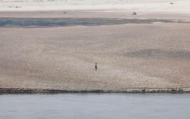 A boy runs on a dried up reservoir on the Mekong River during a drought affecting the Thai-Lao border area of Wiang Kaen district