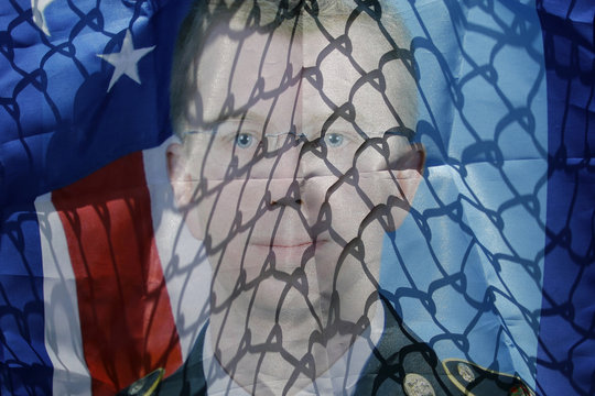 A chain link fence casts shadows on a banner of Manning, a central figure in the Wikileaks case, as protesters rally to call for his release, outside the gates at Fort Meade, Maryland