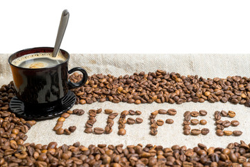 A cup of coffee is on the table. Background. Texture. Spilled coffee beans.