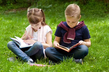 Little school children read a book in nature. Smart little pupil.