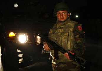 A Turkish soldier with the NATO-led ISAF keeps watch at the site of a suicide car bomb in Kabul