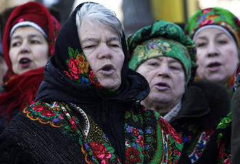 Women sing the anthem during a memorial service in Kiev