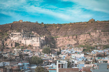 Bundi cityscape, travel destination in Rajasthan, India. The majestic fort perched on mountain slope overlooking the blue city.
