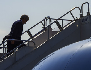 U.S. Secretary of State John Kerry walks up the steps to his aircraft as he leaves Tokyo