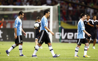 Argentina's Mascherano, Burdisso and Messi leave at the end of their World Cup 2014 qualifying soccer match against Venezuela in Puerto La Cruz