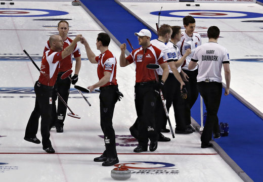 Canadian players celebrate as Denmark leaves the ice  following their page playoff game at the World Men's Curling Championships in Victoria