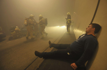 """Firefighters remove car as man playing casualty sits on ground during """"Together 2013"""" exercise in Karavanken tunnel near Jesenice"""