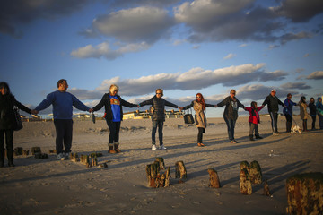 People hold hands during a remembrance ceremony along the beachfront damaged by hurricane Sandy in October 2012 in the borough of Queens in New York