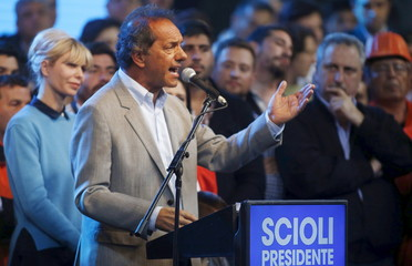 Argentina's ruling party candidate Scioli speaks next to his wife Karina during his final campaign rally in Buenos Aires