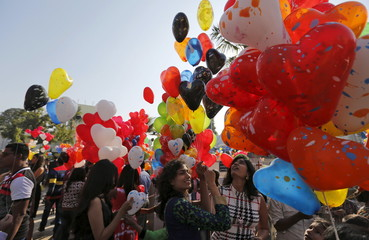 People hold balloons during the New Year celebrations outside a church in Ahmedabad