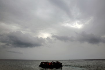 Syrian refugees in an overcrowded dinghy approach a beach after crossing part of the Aegean Sea from Turkey to the Greek island of Lesbos