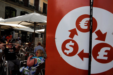 Tourists sit at a terrace next to currency signs in Madrid