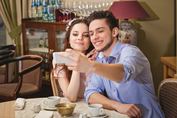 Young enamored couple sitting at a table in a cafe and making selfie