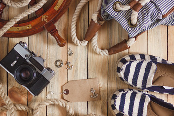 Striped slippers, camera, bag and maritime decorations, top view