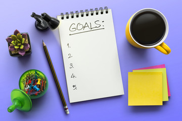 Top view notebook with goals list. Notepad on office table with a cup of coffee, plant, stationery and office supplies. Top view desk, flat lay violet background concept.