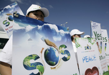 Activists of The Supreme Master Ching Hai International Organization hold signs urging people to turn vegetarian as they believe it will save the planet, in Cancun