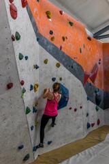 Girl climbing a boulder wall