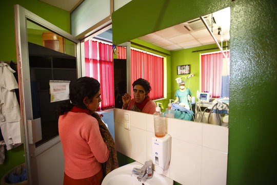 Budhathoki looks in a mirror as her daughter receives laser hair removal treatment at Dhulikhel Hospital in Kavre