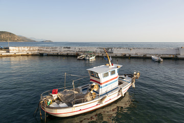small fishing boat in harbor of agios nicolaos on greek peloponnese with sea and mountains in the background