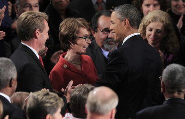 Representative Gabrielle Giffords is greeted by U.S. President Barack Obama as he arrives to deliver the State of the Union address to a joint session of Congress on Capitol Hill in Washington