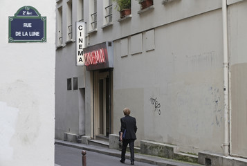A man walks past the entrance of Le Beverley adult cinema in Paris