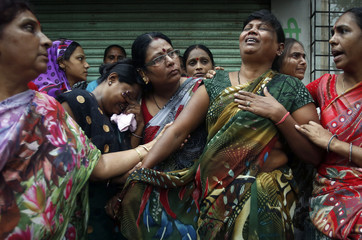 Relatives of residents trapped under the rubble react at the site of a collapsed residential building in Mumbai