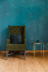 Dark green soft armchair near plaster wall. Arm-chair with fabric upholstery and big vintage mirror in loft style interior