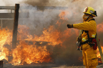 A firefighter gestures as flames from a wildfire burn at a horse ranch in Lancaster, California