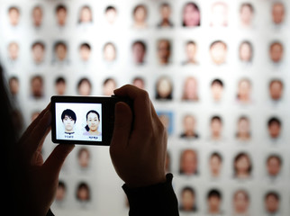 A visitor takes pictures of Japan's figure skaters from a board displaying profile shots of the Japanese team for the Sochi 2014 Winter Olympic Games, in Tokyo