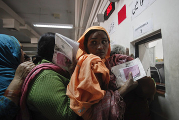 Women stand in queue to receive free medication from a pharmacy at the Punjab Institute of Cardiology (PIC) in Lahore