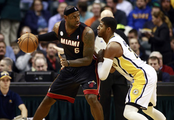Miami's LeBron James moves on Indiana's Paul George during an NBA basketball game in Indianapolis.