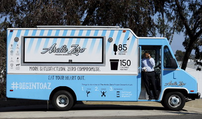 Arctic Zero Chief Executive Amit Pandhi talks on the phone at the entrance of his healthy frozen dessert ice cream truck in San Diego