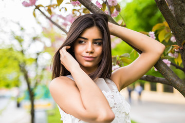 beautiful young woman take photo with blooming cherry blossoms sakura flowers