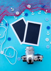 Top view composition - Blank paper photo frames with starfish, shells, coral and items on wooden table. camera, Concept of remembrance and nostalgia in summer tourism, travel and vacation. blue color