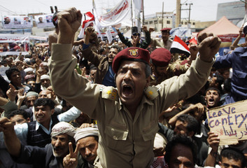 An army officer shout slogans along with anti-government protesters during a rally in Sanaa University