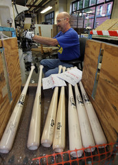 Danny Forrest stamps the Louisville Slugger and World Series logos on bats in Louisville
