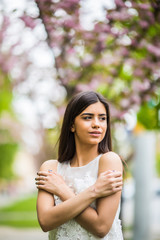 beautiful young woman with blooming blossoms sakura flowers