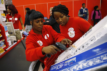Target employees Cage and Isom help check out Thanksgiving Day shoppers at a Target store in Chicago