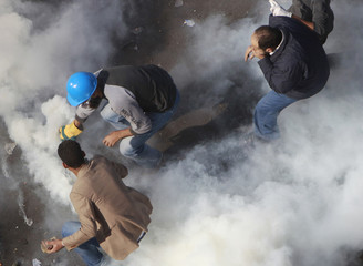 Protesters stand amidst tear gas fired by riot police at Tahrir Square in Cairo